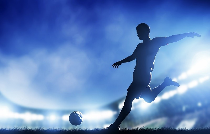 Football, soccer match. A player shooting on goal. Lights on the stadium at night.