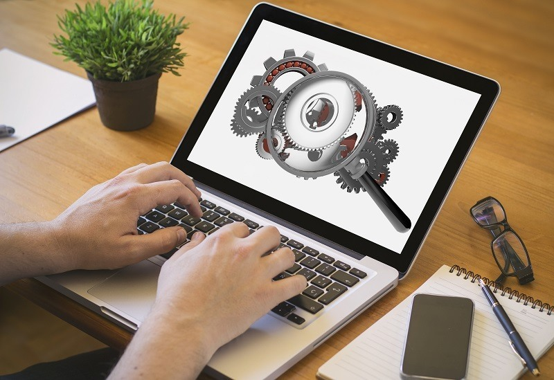 Developer or web designer at work. Close-up top view of man working on laptop with magnifying glass analyzing gears on screen. all screen graphics are made up.
